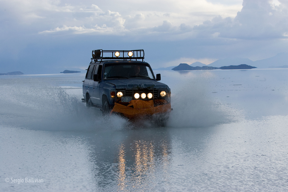 Travelers drive their SUV across a the Salar de Uyuni, a flooded salt flat,  in Bolivia