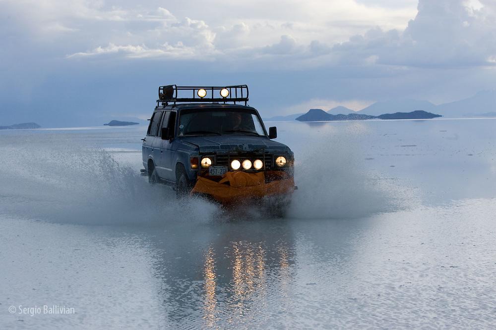 Travelers drive their SUV across a the Salar de Uyuni, a flooded salt flat,  in Bolivia