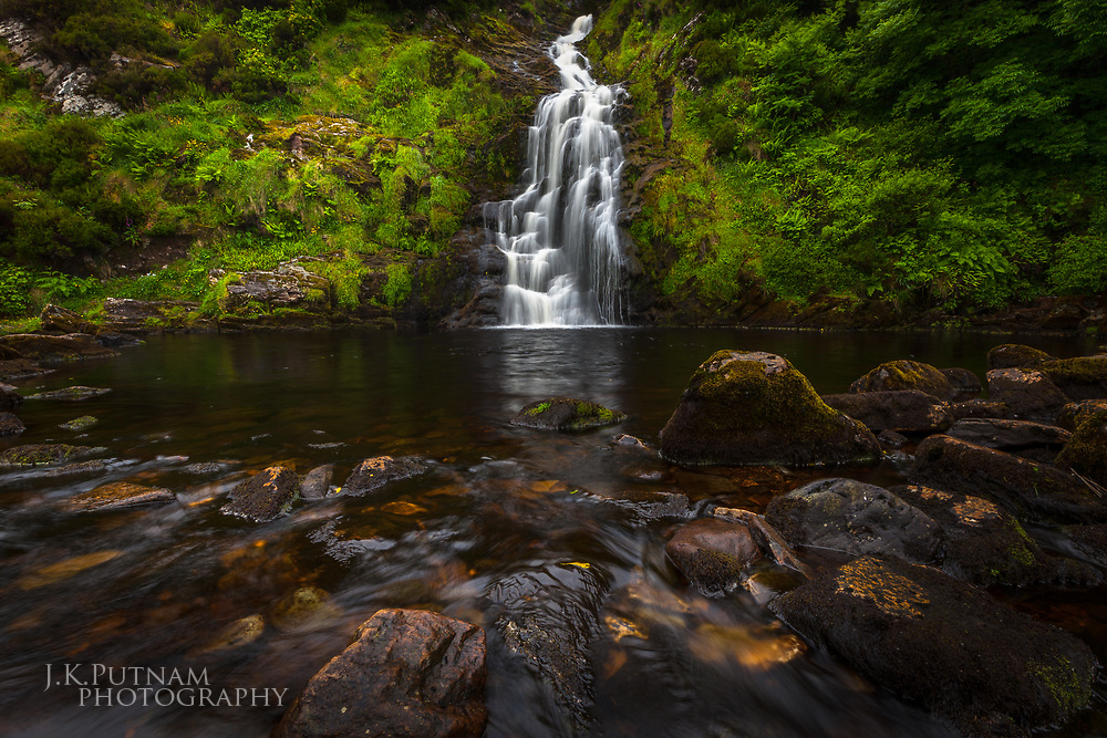 A waterfall cascades down a lush, rocky hillside near Mahares Beach in Ireland.