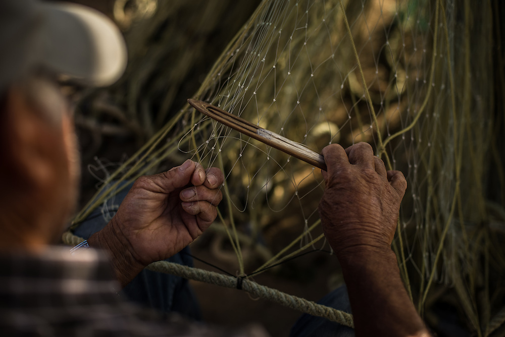 COCHOLGUE, CHILE - MARCH 19, 2014:  Luis Sanhueza, 73, mends a fishing net in Cocholgue, a small fishing village near Concepcion, Chile.  PHOTO: Meridith Kohut for The World Wildlife Fund