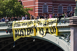"ter, London, May 30th 2015. Anti-austerity campaigners bring traffic on Westminster Bridge as they paint and hang a banner off the bridge highlighting an alleged £120 billion owed in taxes as compared to the proposed £12 billion cuts to welfare. PICTURED: The banner proclaiming ""Austerity is a lie"" hangs off Westminster Bridge, facing Parliament."