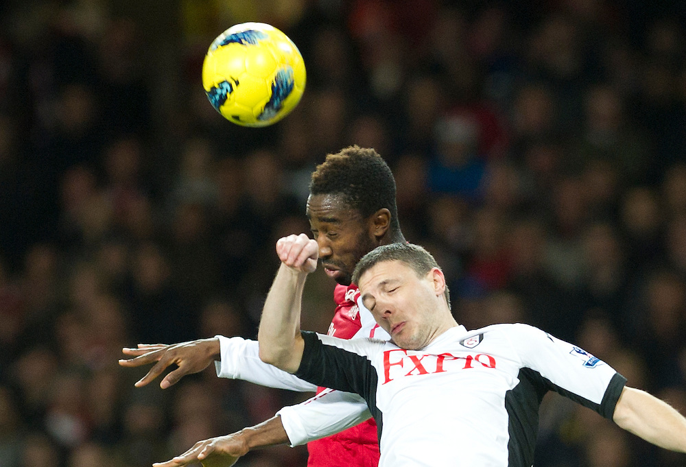 Arsenal's Alexandre Song fights for the ball with Fulham's Chris Baird during  their English Premier League  soccer match at the  Emirates stadium in London, Saturday, Nov. 26, 2011. (AP Photo/Bogdan Maran)