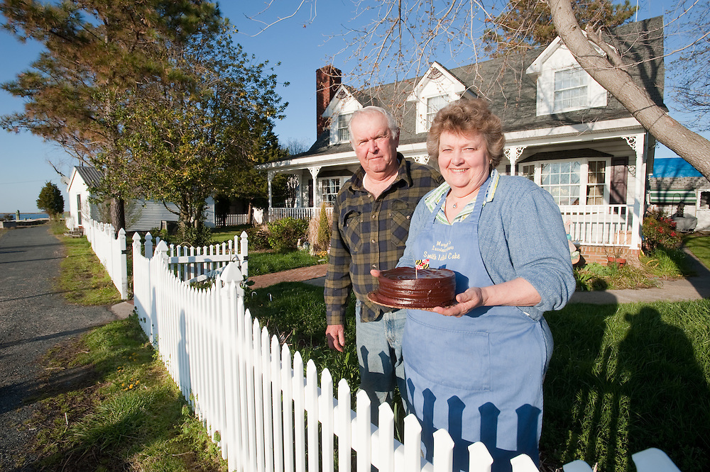 Woman holding her Smith Island Cake with husband by their home in Smith Island