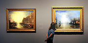 © Licensed to London News Pictures. 13/03/2012. London, UK. A member of The National Gallery staff looks at the oil painting 'Keelmen Heaving in Coals by Night, 1835' by British painter, Joseph Mallord William Turner. The National Gallery's spring exhibition, Turner Inspired: In the Light of Claude. It is the first major exhibition to look at the influence of Claude on Turner. The exhibition runs 14 March - 5 June 2012.  Photo credit : Stephen SImpson/LNP