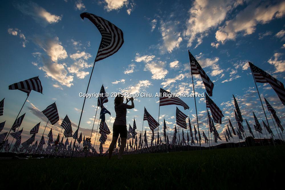 9月10日,在美国加利福尼亚州洛杉矶的马里布,一名女子在旗帜中间拍照。当天,在美国&ldquo;9&middot;11&rdquo;事件十四周年前夕,佩珀代因大学的学生和教职员工在学校草坪上插起约3000面美国国旗,纪念&ldquo;9&middot;11&rdquo;事件遇难者。新华社发(赵汉荣摄)<br /> A woman takes pictures amongst 3,000 US flags are displayed at Pepperdine University to mark the 14th anniversary of the 9/11 terror attack, September 10, 2015 in Los Angeles, California, the United States. (Xinhua/Zhao Hanrong)Photo by Ringo Chiu/PHOTOFORMULA.com)