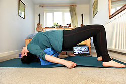 Life in coronavirus lockdown in the UK April 2020. A woman practices yoga at home with an online lesson. Model released