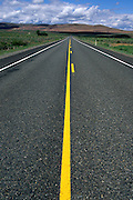 road with yellow strip heading off to the distant mountains in the Western United States