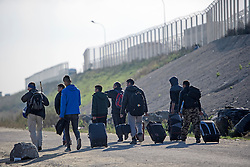 © Licensed to London News Pictures. 25/10/2016. Calais, France.  A group of migrant men carrying all of their belongings, walk past a fenced area and passing lorries as they leave the migrant and refugee camp in Calais, known as the 'Jungle'. French authorities have moved thousands of refugees and migrants living at the makeshift living area on the French coast, with some still refusing to leave. . Photo credit: Ben Cawthra/LNP