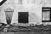 Nederland, Ooij, 01-02-1995Eind januari, begin februari 1995 steeg het water van de Rijn, Maas en Waal tot record hoogte van 16,64 m. bij Lobith. Een evacuatie van 250.000 mensen was noodzakelijk vanwege het gevaar voor dijkdoorbraak en overstroming. op verschillende zwakke punten werd geprobeerd de dijken te versterken met zandzakken. Hier een nooddijk langs de Maas met zandzakken voor de deur.Late January, early February 1995 increased the water of the Rhine, Maas and Waal to a record high of 16.64 meters at Lobith. An evacuation of 250,000 people was needed because of flood risk. At several points people tried to reinforce the dikes with sandbags. Foto: Flip Franssen/Hollandse Hoogte