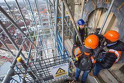 @Licensed to London News Pictures 27/11/2018.Canterbury, Kent. Local BBC TV interview Mark Crangle, clock maker on the outside of the south west tower of Canterbury Cathedral. The Cathedral Clock built in 1855  and housed on the south west tower of Canterbury Cathedral is being dismantled ready to be renovated and re-guilded. The clock face weighing 78 kilos and measuring 8 feet in diameter is being shipped to the Cumbrai Clock Company in Penrith and will be absent from the cathedral for 18 months. Photo credit: Manu Palomeque/LNP