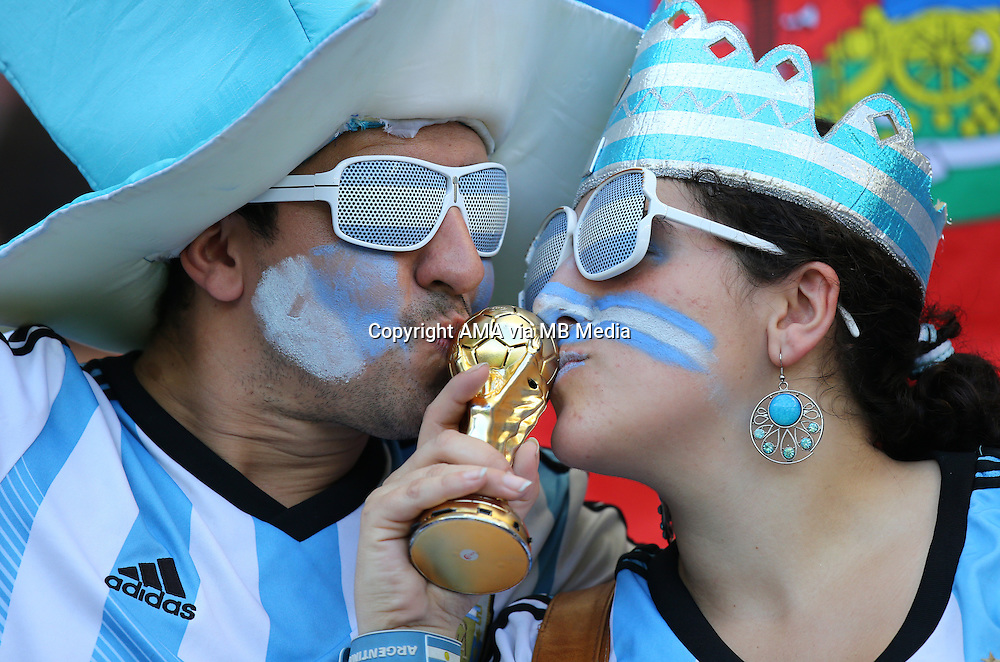 Fans of Argentina with painted faces kiss a replica World Cup Trophy