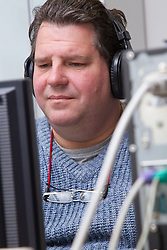 Computer class for people with visual impairments - man using headphones for audio.