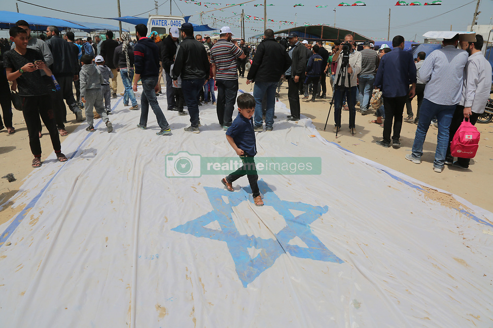 April 13, 2018 - Gaza, Gaza strip, Palestine - Palestinians walk on an Israeli flag during a protest demanding the right to return to their homeland, at the Israel-Gaza border, east of Gaza City. (Credit Image: © Majdi Fathi/NurPhoto via ZUMA Press)