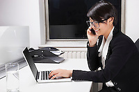 Side view of young businesswoman using laptop and cell phone at desk in office