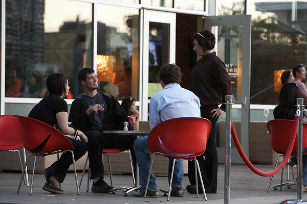 Stock photo of a group of young adults at a patio table ordering at The Grove restaurant