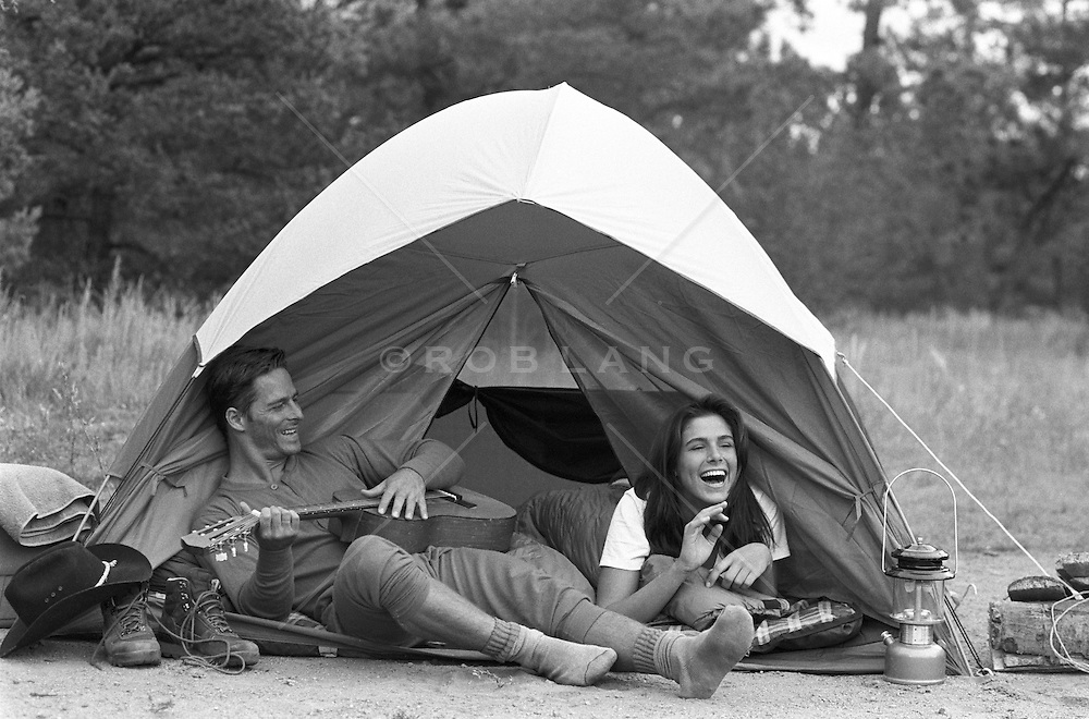 Man and woman enjoying camping out and playing guitar out in a field