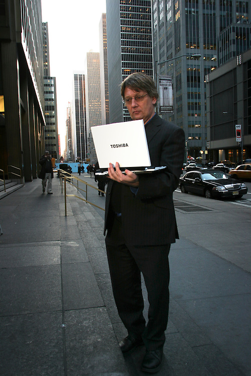 Paul Taylor reporter for the Financial Times, standing in the 54th street Manhattan next to the Financial Times offices with Toshiba R 400 laptop, at Tuesday February 06 2007...Paul Taylor cheek the new gadgets of Toshiba R400, like touch screens that can also tern around and a finger print ID for the computer...