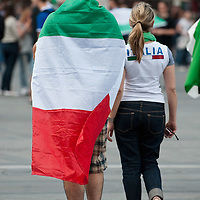 MILAN, ITALY - JUNE 14:  An Italian fan wearing Italy national flag walks hand in hand with a girl wearing an Italia Tshirt in Piazza del Duomo while watching the football match on the maxi screen on June 14, 2010 in Milan, Italy. Italy's national football team managed a draw 1-1 against Paraguay in their first match of FIFA 2010Soccer World Cup.