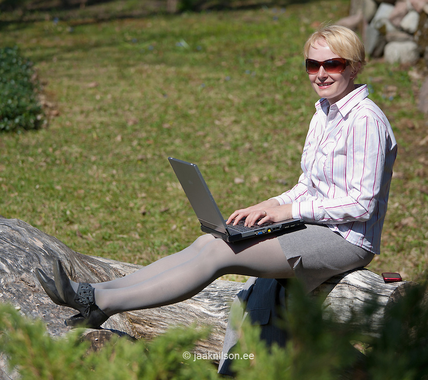 Smiling Businesswoman Sitting on Log and using  Laptop Computer