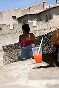 woman sitting in the shadow with a snow cone ice cream in the foreground