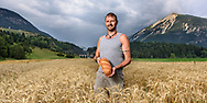 The organic farmer Gordo Simeon in a field of common wheat on a cloudy summer evening in August with the Landwasser viaduct and the mountain Muchetta in the background, Parc Ela, Grisons, Switzerland