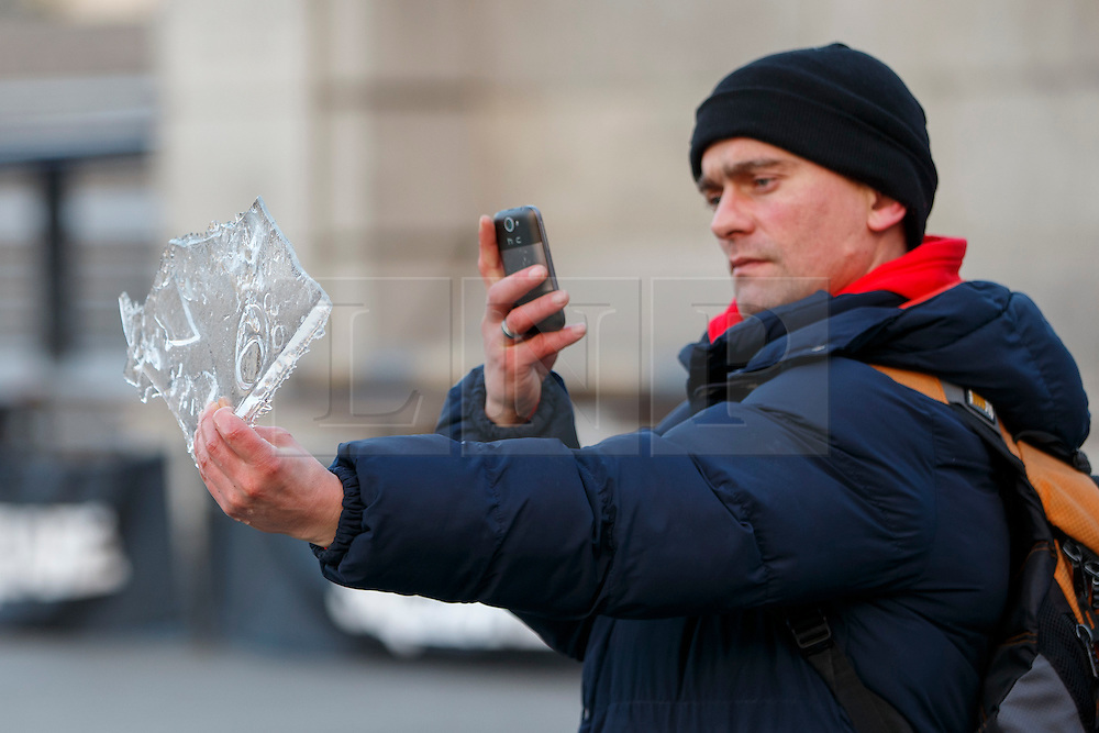 © Licensed to London News Pictures. 20/01/2016. London, UK. A commuter takes a picture of a piece of ice taken from the fountains in Trafalgar Square which covered in a layer of ice after temperatures in the capital dropped as low as -3C on Wednesday, 20 January 2016. Photo credit: Tolga Akmen/LNP