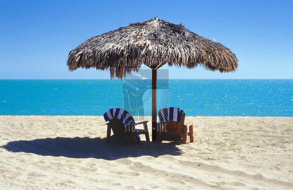 tiki umbrella with two Adirondack chairs on the beach