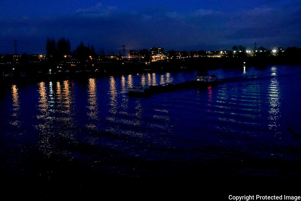 Nederland, Amsterdam, 14 december 2017<br />Een binnenvaartschip vaart over het Amsterdam-Rijnkanaal heen, gezien vanaf de Nesciobrug. Opde achtergrond zijn de lichtjes van IJburg te zien.<br />Foto: Amber Beckers/Hollandse Hoogte