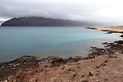View over calm sea to clouds Risco de Famara cliffs, Graciosa island, Lanzarote, Canary Islands, Spain
