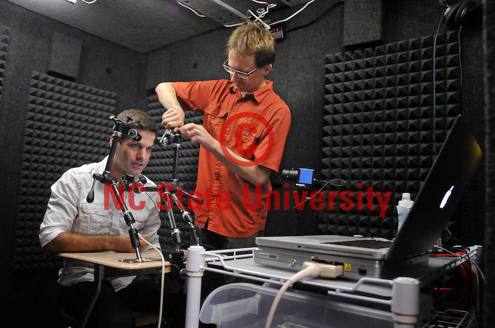 CHASS researcher Jeff Mielke (right) and Christopher Carignan (left) run a diganostic test on ultra-sound and aerodynamic-flow equipment used to measure speech production in the phonology lab in Cox Hall.