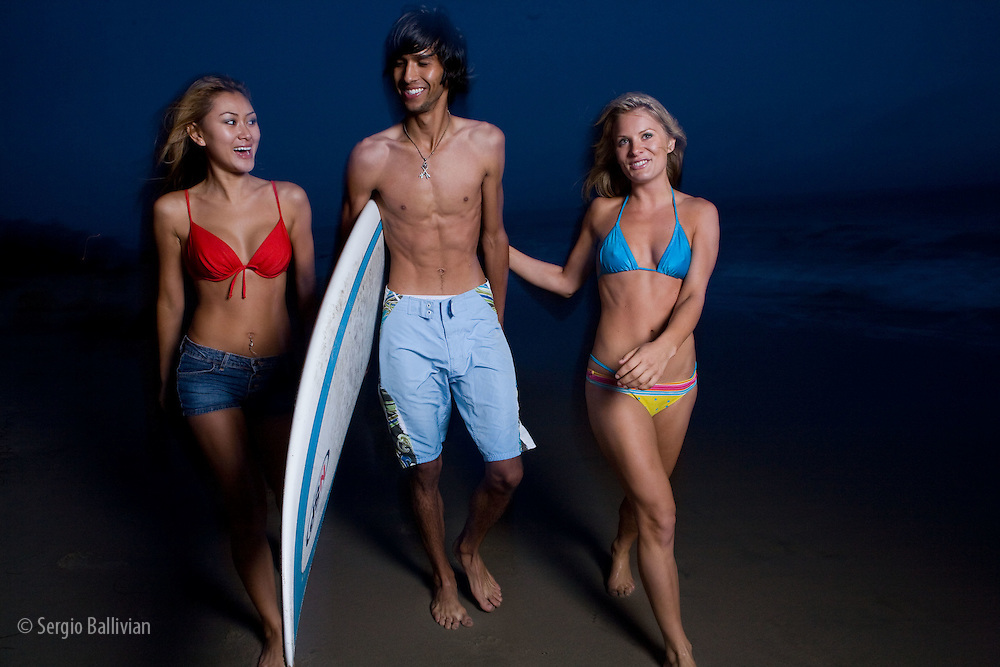Lifestyle portraits of a young male surfer and two young women on a beach in Malibu Beach, CA