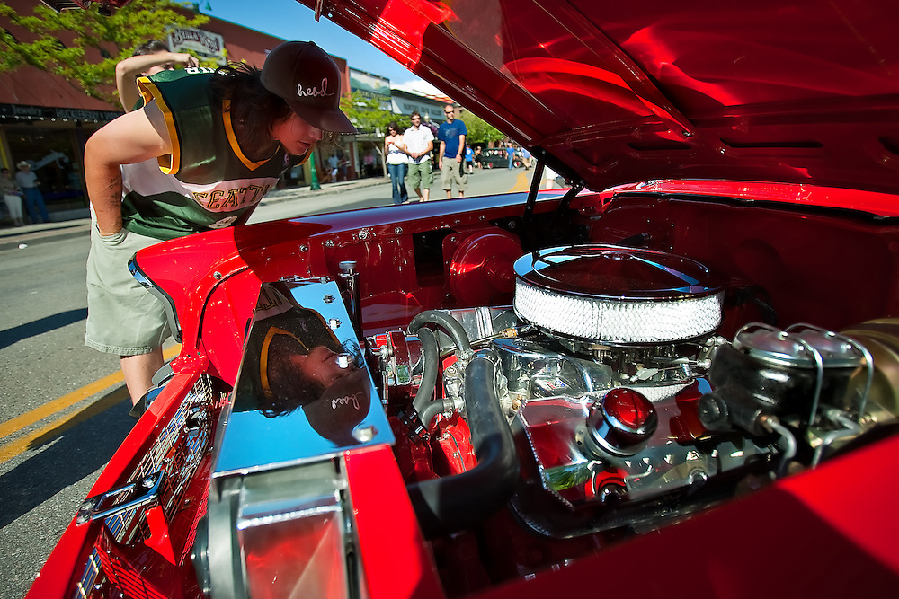 BEN BREWER/Press Adam Boren of Spokane pokes his head under the hood of Brad Hoyt's Red two-door hardtop 1957 Chevrolet Bel Air Saturday afternoon at Car d'Lane on Sherman Avenue.