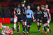Ross Joyce (Referee) shows a yellow card to Liam Lindsay of Barnsley (6) for a foul on James Coppinger of Doncaster Rovers (26) during the EFL Sky Bet League 1 match between Doncaster Rovers and Barnsley at the Keepmoat Stadium, Doncaster, England on 15 March 2019.