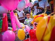 28 OCTOBER 2015 - YANGON, MYANMAR: A boy looks at inflatable toys for sale during observances of Thadingyut at Botataung Pagoda in Yangon. Botataung Pagoda was first built by the Mon, a Burmese ethnic minority, around the same time as was Shwedagon Pagoda, over 2500 years ago. The Thadingyut Festival, the Lighting Festival of Myanmar, is held on the full moon day of the Burmese Lunar month of Thadingyut. As a custom, it is held at the end of the Buddhist lent (Vassa). The Thadingyut festival is the celebration to welcome the Buddha's descent from heaven.    PHOTO BY JACK KURTZ