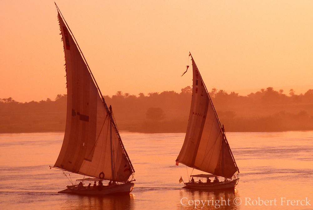 EGYPT, NILE RIVER Feluccas, traditional sailing ships on the Nile near Luxor with the  West Bank beyond