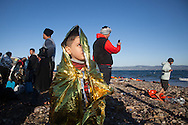 A Syrian boy stands on a beach near Molyvos, Lesvos island in Greece, wearing a foil blanket designed to prevent wind and create warmth.