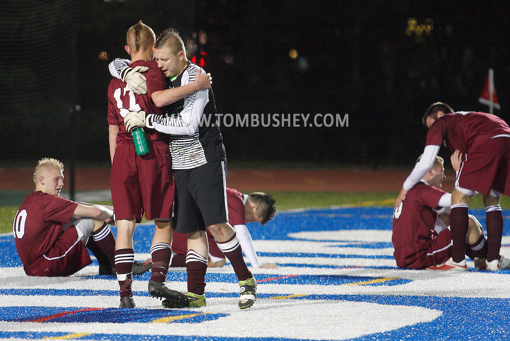 Fort Ann goalie Jonah Gould hugs Nick Lehoisky (17) after Chazy scored in the second overtime periold to defeat Fort Ann 2-1 in the Class D state semifinals at Faller Field in Middletown on Saturday, Nov. 16, 2013. (Tom Bushey – Special to The Post-Star)