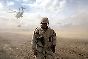 US MARINE MAJOR MICHAEL CALLAHAN,turns away from the rotor wash of the helicopter as it prepares to drop water for a water distribution point in the city of Tikrit for all the locals who had fled the city and now trying to get backto thier lives in  Tikrit.