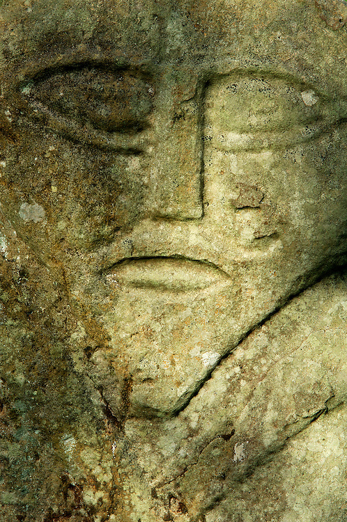 Caldragh cemetery on Boa Island, Lower Lough Erne, Ireland. Ancient Celtic prehistoric carved stone face called the Janus stone.