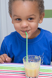 Little boy drinking fruit juice from a glass with a straw,