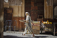 A traditional dressed woman walks in the medina of Fés, Morocco.