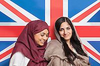 Happy young Muslim women in traditional clothing standing against British flag
