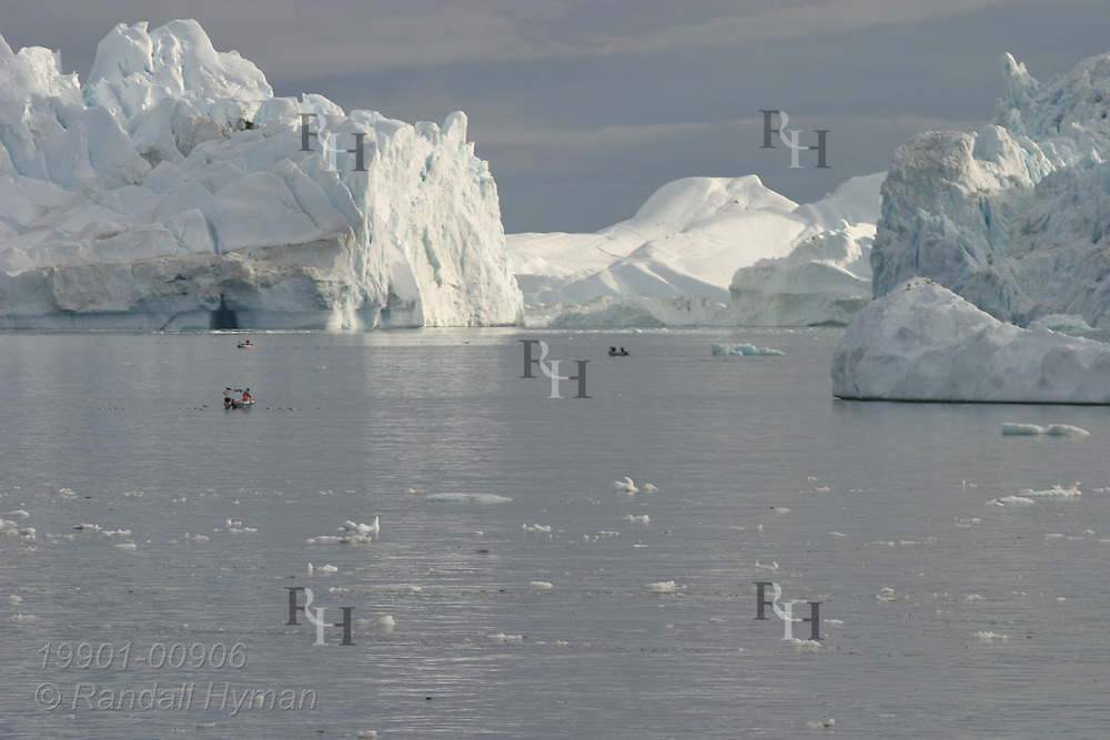 Fishing boats are dwarfed by massive icebergs at mouth of Ilulissat Kangerlua Icefjord in Disko Bay, Greenland.