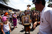 a man bring the portrait of Anak Agung Niang Rai in Pelebon ceremony of Anak Agung Niang Rai of Puri Agung Ubud, The wife of King Of Ubud. Pelebon Ceremony or  Ngaben ceremony is a ceremony to purify and return the  five element of the universe that form the life itself in human body to the universe.