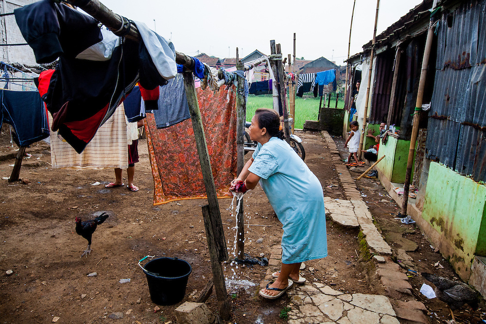 A local resident of Cilawengke hang clothes that were washed with water contaminated by toxic wastes. Residents could only afford to purchased water for drinking and cooking. Many suffer from skin problems...Credit: Andri Tambunan for Greenpeace