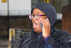 London, August 31st 2015. Getting soaked, mayoral candidate Diane Abbot takes a call as revellers ignore the inclement weather to enjoy day two of the Notting Hill Carnival.