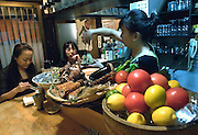 Chizuru Doi pours drinks for customers at Enoki, a bar-cum-eatery she has run for some 25 years in Nonbeiyokjocho, or Drunkard's Alley, in trendy Shibuya district, Tokyo. Bottles of Japanese shochu bought by regular customers at Enoki are named and stored on the shelves of the tiny bar-cum-eatery in Nonbeiyokocho, or Drunkard's Alley, in Nonbeiyokocho began life immediately after World War II as group of tea houses. Though the alley is just a short walk from the central Shibuya shopping district, the rents are low due to the area being built over a river. Today 47 eateries, each with barely enough room to swing a cat, serve beer, fine wines and good, inexpensive fare.