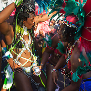 Four dancers whine and grind to the music. The Notting Hill Carnival has been running since 1966 and is every year attended by up to a million people. The carnival is a mix of amazing dance parades and street parties with a distinct Caribbean feel.