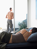 Woman lying on bed in front of man standing on balcony back view