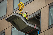 Steel worker untying crane hook from staircase at Rimmerman offices for D. Kelly Construction